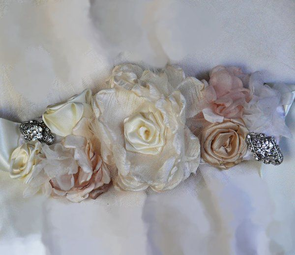 Haute courture ivory bridal sash with blush and rhinestone brooch accents.