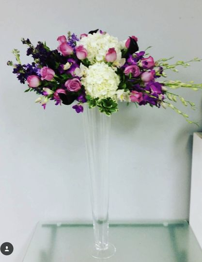 Tall centerpiece including roses, hydrangea, orchids, stock and calla lilies