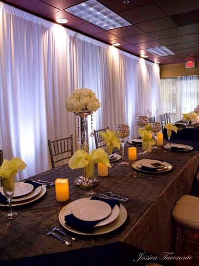 Private restaurant space with wall drape and uplighting in white