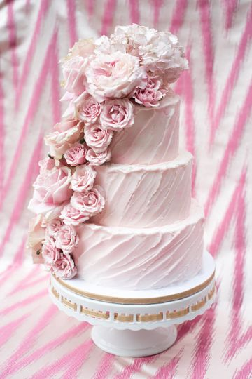 This three tiered wedding cake by Glass Slipper Cakes was accented with pink roses