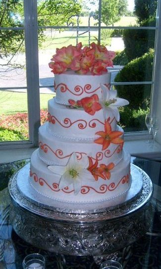 Buttercream cake with tangerine scrollwork, completed with silk flowers matching the bride's...