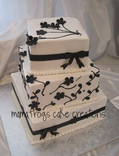 Square buttercream cake, slightly offset, black fondant ribbon, bows and flowers