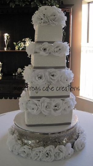 This beautiful 4 tier square cake is adorned with silk white roses between the tiers. Each rose has...