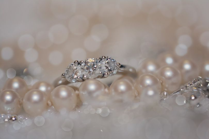 Photo of the bride's engagement ring along with the first piece of jewelry she ever received from...