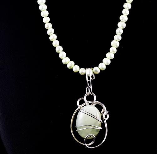 Jade pendant wrapped in swirls of sterling silver and suspended from a strand of matching pearls.