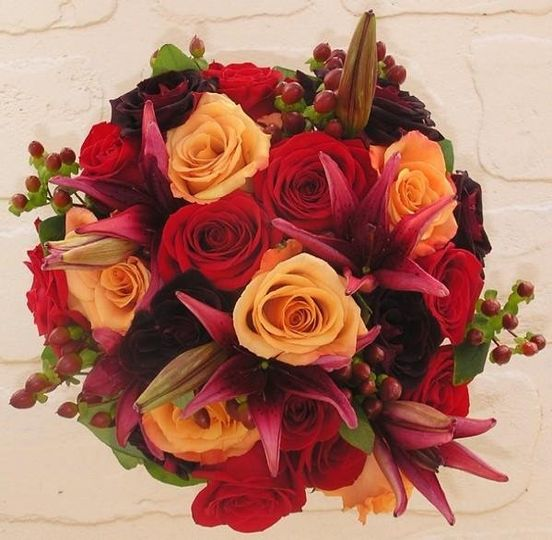 Bride's bouquet with red, burgundy  and orange roses, burgundy lilies and hypericum.