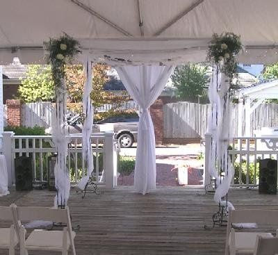 Chuppah with arrangements on the top corners.