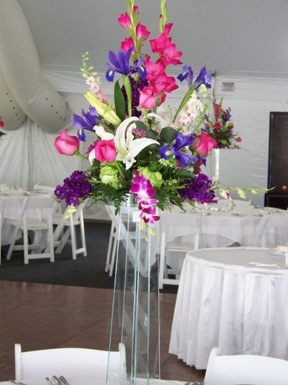 A complimentary centerpiece created in a clear container and set high on a glass tower....