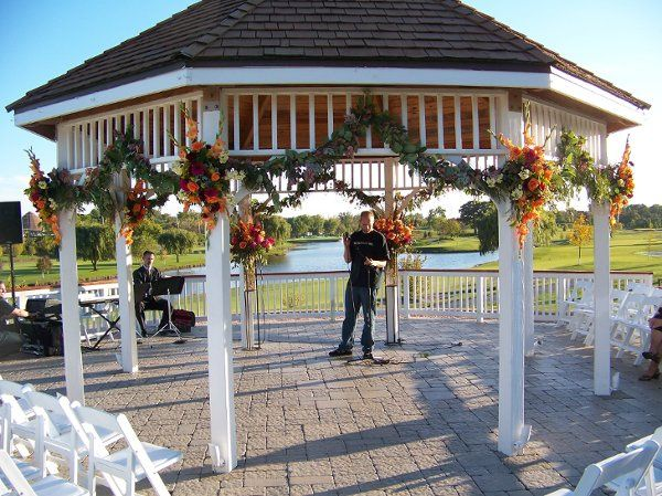 The gazebo at Palos Country Club, decorated with rich fall tone flowers and garland for an October...