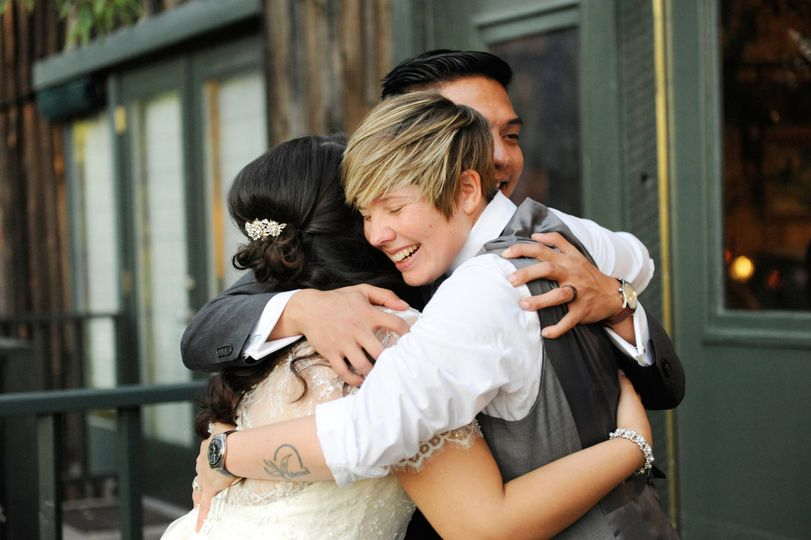 Officiant hugging the couple