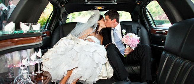 bride and groom kissing in limo
