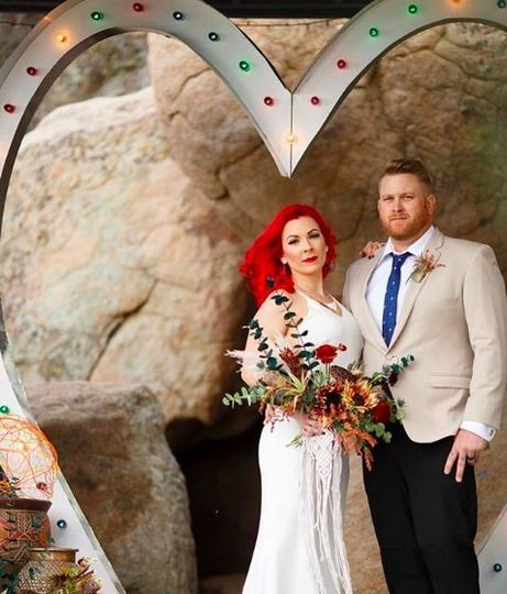 Newlyweds and heart backdrop