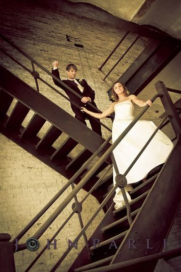 Bridal portrait of bride and groom on old staircase at Rockford IL's Prairie Street Brewhouse.