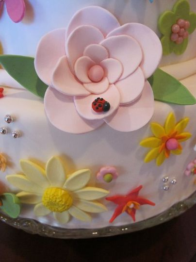 Handmade whimsical sugar paste flower with a little ladybug on one of the petals.
