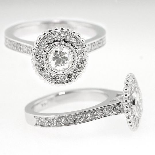 This Jill Lynn custom designed engagement ring features an old European cut diamond bezel set center...