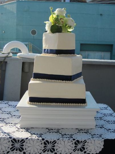 3 tiered square offset in smooth butter cream with satin ribbon and fondant pearl accents.