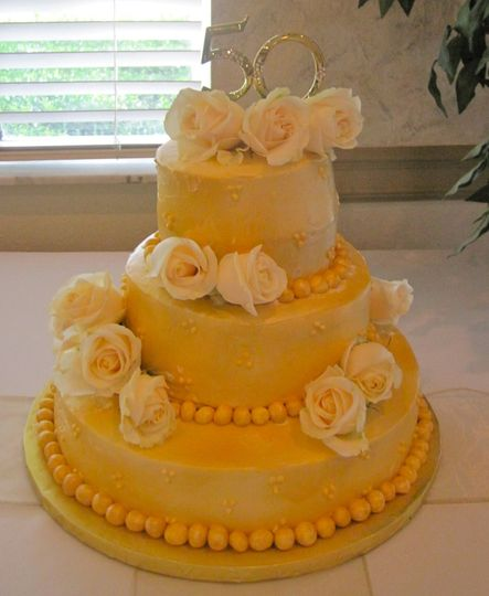 This is a Golden 50th Anniversary Cake with white cottage roses. The top tier was butter pound cake...