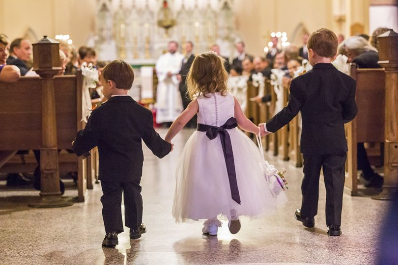 Children holding hands down aisle