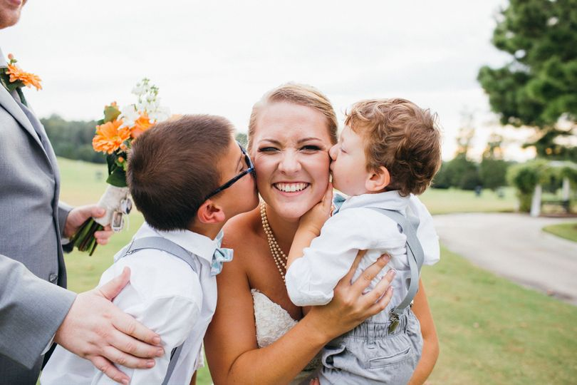 Children kissing the bride on the cheeks