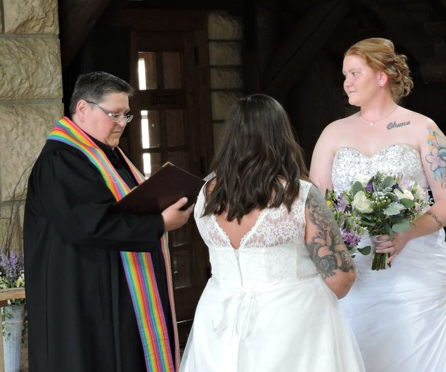 The officiant with the lovely brides