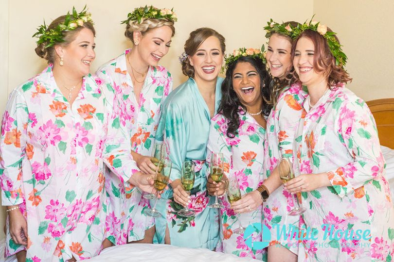 Bride and her Bridesmaids pose for a toast before getting dress at the Hilton hotel and resort in...