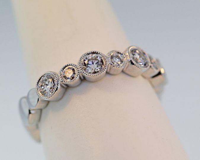 18k white gold diamond wedding band with diamonds half way arround. Each diamond is bezel set with a...