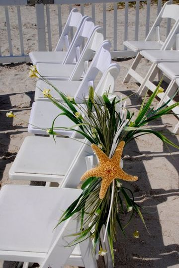 Chair cap of silk sea grass with white sand dollar on row of chairs at a beach wedding in Florida.