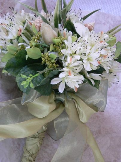 Bouquet that never wilts. Shells with silk flowers.  Wrapped in two tones of silk ribbon and french...