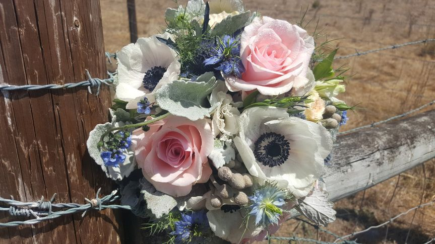 Country bouquet featuring garden roses, anemone, brunia balls and dusty miller.