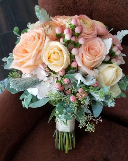 Summer bridal bouquet featuring roses, ranunculus, berries, eucalyptus
