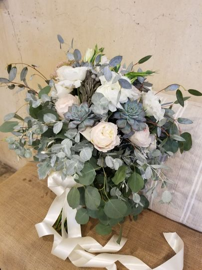 Leafy greens with white garden roses, ranunculus and succulents. Long satin ribbon.