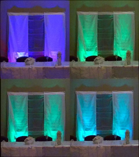 Uplighting behind the head table at a wedding reception. The lights were in color-changing mode, so...