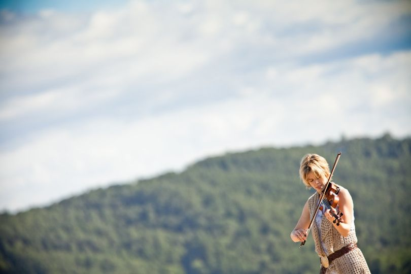 Mountain backdrop behind the violinist