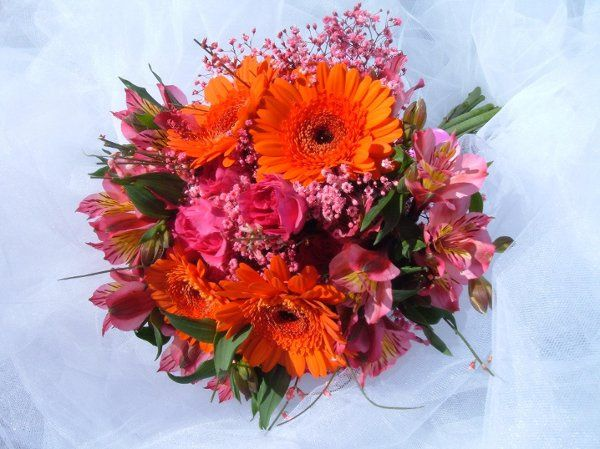 A stunning mix of orange mini gerbera daises, hot pink spray roses, peruvian lilies and pink...