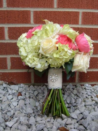 Beautiful upscale look of fresh green hydrangea, virginia roses, and french garden roses are hand...
