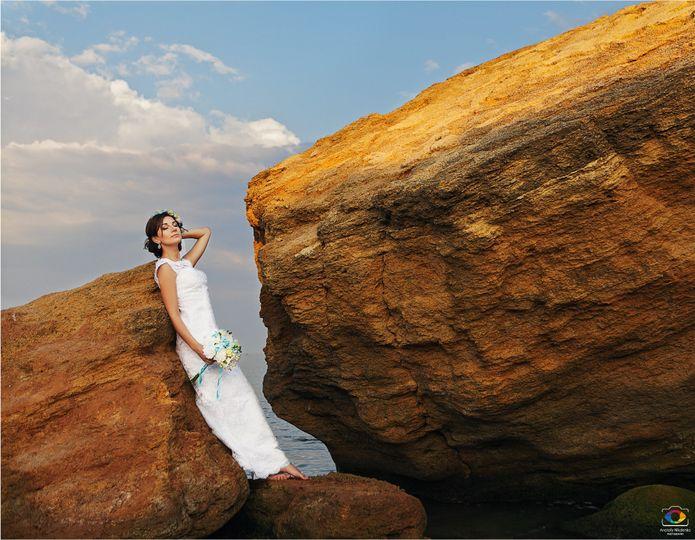 Bride posing beside cliff