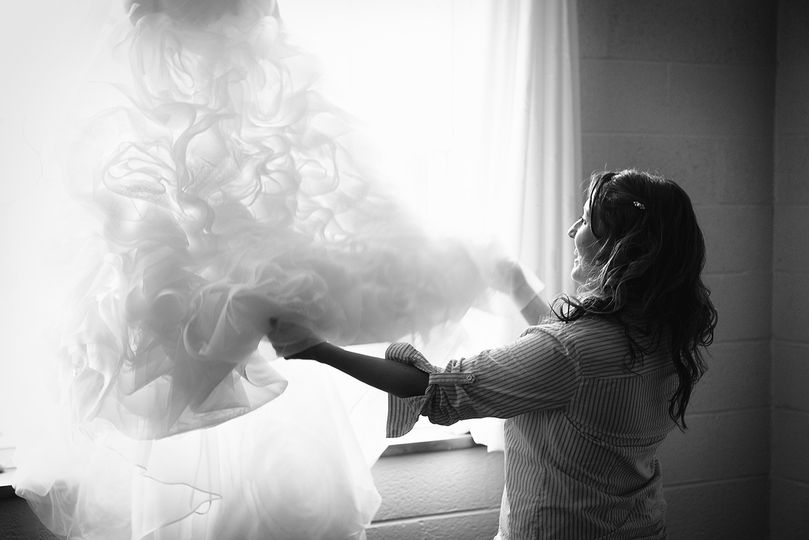 The bride's excitement and happiness is so obvious here as she gets ready to put on her wedding gown...