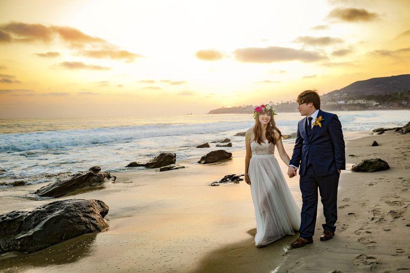 Newlyweds walking along the shore