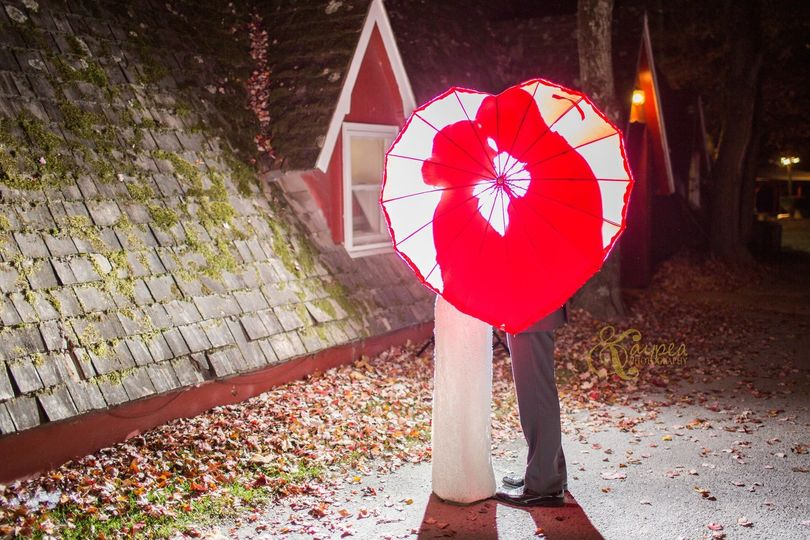 Newlyweds behind a heart-shaped parasol