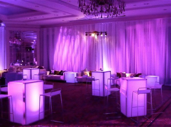 Glowing pedestal high-top tables, chic bar stools, white velvet couches, and tall sheer white drape....
