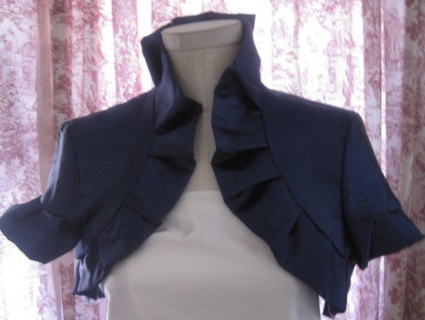 This shrug is made of 100 percent silk satin. The hand pleated detail is stitched around the entire...