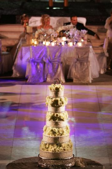 The wedding cake was spotlighted at one end of the dance floor with the newlywed couple seated at...