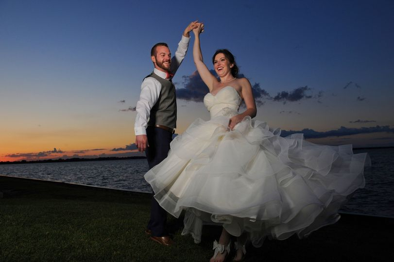 Couple dances on the waterfront shore at sunset after their Marine wedding.