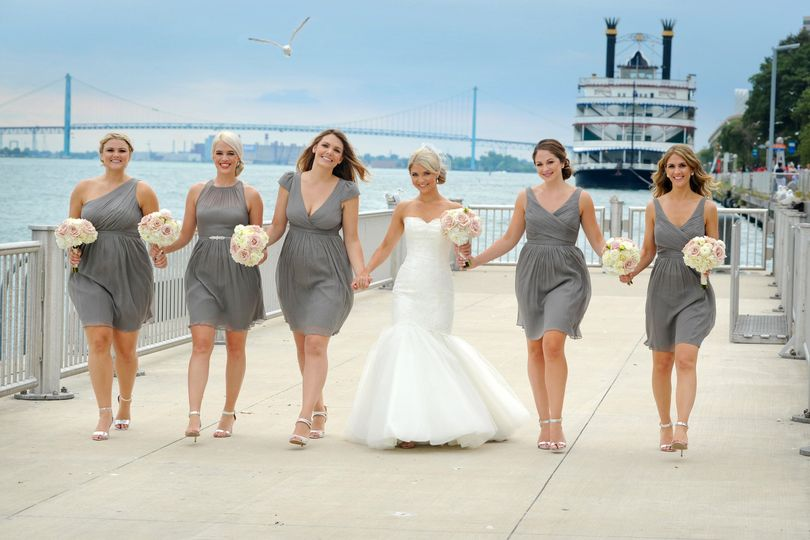 Brides walk along the boardwalk downtown Detroit, Michigan in front of the Waterview Loft.