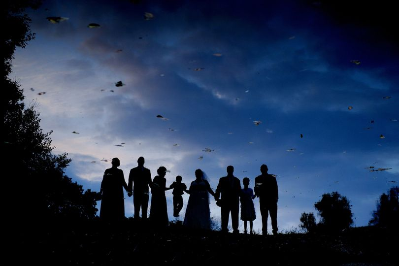 The wedding party are seen reflected in a pond at their Detroit area fall wedding at twilight.