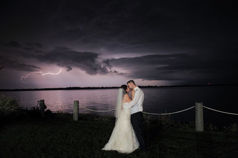 A couple kiss lakeside during a summer lightening storm in Michigan.