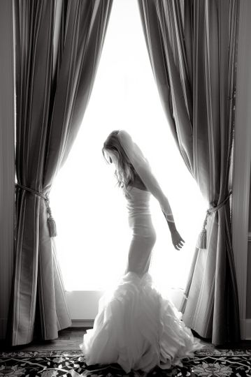 A bride walks over to the window for a photo in Detroit, Michigan.