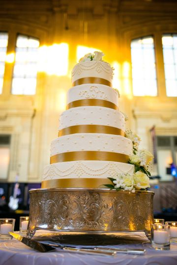 White wedding cake with gold ribbons