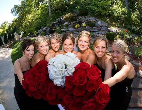 bride and bridesmaids with red rose bouquets