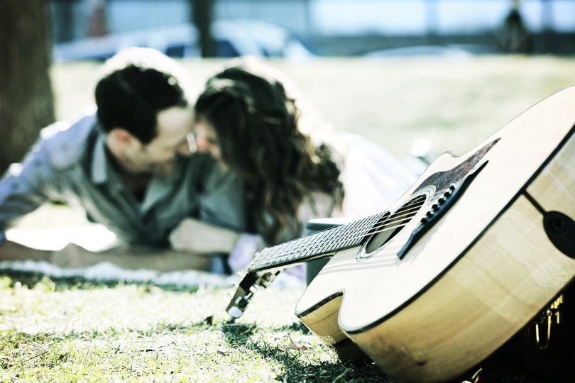A couple embrace near a guitar